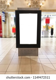 Centered blank empty portrait light box information board with blurred store background ideal for display advertisement signage, digital space, mall ads