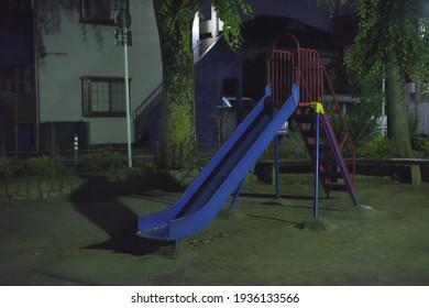 Composition centrale d'un toboggan dans une aire de jeux dans un parc sans personne à l'extérieur la nuit au Japon.