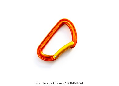 Centered orange solid bent gate carabiner (karabiner) used for clipping the rope in, isolated on white background, with copy space. Basic climbing gear with axis strength ratings.