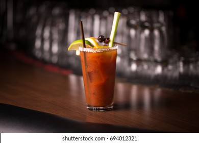 Centered traditional vodka tomato juice bloody mary mix cocktail in salted rim tumbler garnished by lemon with olive and celery stalk on retro diner bar with blurry stacked glass restaurant background