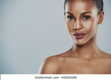 Centered view of beautiful grinning African bare shouldered female with short hair and seductive expression and over gray background