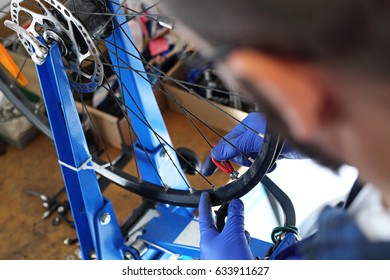 Centering the wheels. The mechanic in the bike service repairs the wheel in the bike.
