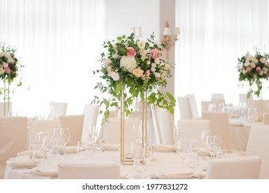 Centerpiece made of green leaves and fresh flowers stands on the dinner table. Wedding day. Fresh flowers decorations. Peach and awhite weddnig decorations.
