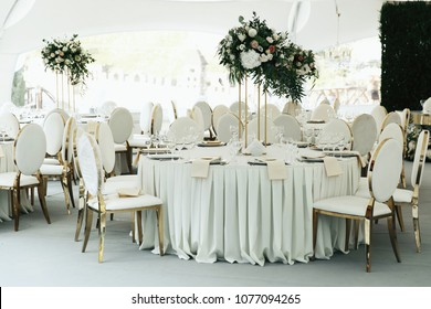 Centerpiece made of green leaves and roses stands on the dinner table number eight