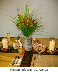 Centerpiece at Thanksgiving Table with flower bouquet, candles, drinks, leaves