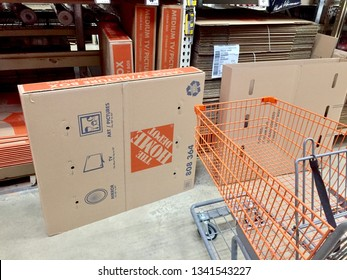 Centerville, Virginia - March 10, 2019: A shopping cart sits next to a large cardboard storage box used for televisions or artwork inside a The Home Depot store.