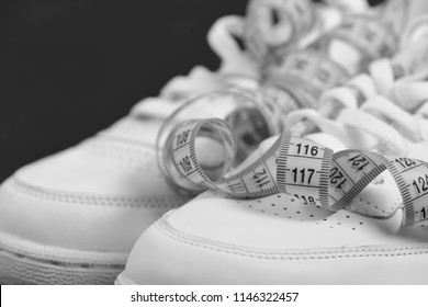 Centimeter in yellow color curled on white trainers, close up. Sneakers with measuring tape on black background. Fitness and sportswear concept. Sport shoes and sportive equipment for healthy shape.