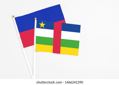 Central African Republic and Haiti stick flags on white background. High quality fabric, miniature national flag. Peaceful global concept.White floor for copy space.