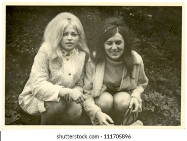 CENTRAL BOHEMIA, CZECHOSLOVAK REPUBLIC, CIRCA 1967 - two girlfriends, taken while kneeling in front of the park bushes - circa 1967 in Central Bohemia