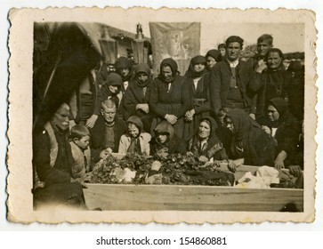 CENTRAL BULGARIA, BULGARIA - CIRCA 1950: Group of old women and a few old men weeping for the deceased in a coffin (village funeral) - Note: slight blurriness, better at smaller sizes - circa 1950