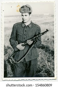 CENTRAL BULGARIA, BULGARIA - CIRCA 1950: Young soldier with a gun - rifle, posing on a field - Note: slight blurriness, better at smaller sizes - circa 1950