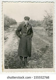 CENTRAL BULGARIA, BULGARIA - CIRCA 1955: Photo of the young soldier in a long coat, he stands on a dirt road - Note: slight blurriness, better at smaller sizes - circa 1955