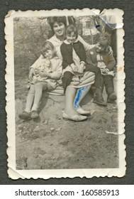 CENTRAL BULGARIA, BULGARIA - CIRCA 1955: Woman with her three children sitting on the ground  circa 1955