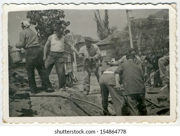 CENTRAL BULGARIA, BULGARIA, district Plovdiv - CIRCA 1960: Group of middle-aged men working in a village (village Brigade) - Note: slight blurriness, better at smaller sizes - circa 1960