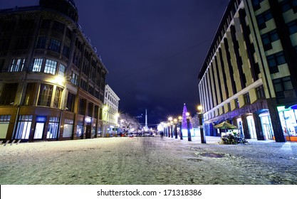 Central crossroad in Old Riga, Latvia at winter night with Monument of Freedom on a background