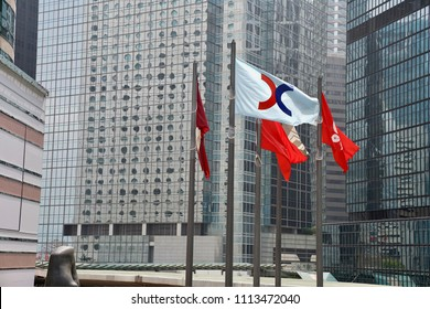 Central, Hong Kong - 15 March 2018: The flags flying at the public plaza outside the Hong Kong Exchange Square, including flag of Hong Kong Land, HK Stock Exchange, National Flag and the HK flag.