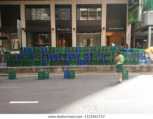 Central, Hong Kong - 27 June 2018: A  worker in progress of delivering bottles of carboy water to the offices and feeling so tired and hot at the street.