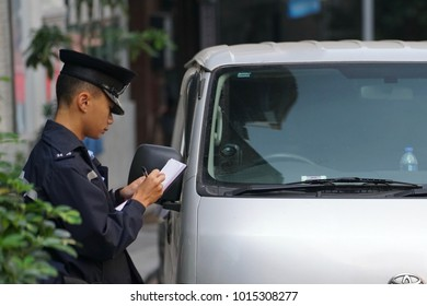 Central, Hong Kong - 8 Dec 2017: A policeman issuing penalty notice against parking contravention.