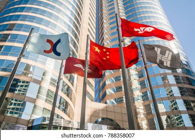 CENTRAL, HONG KONG - DEC 21, 2017: The flags hoisting at the Forum of Exchange Square with skyscrapers in the background. Flags of HKSAR, China,  Hongkong Land and Hong Kong Stock Exchange (HKEx)