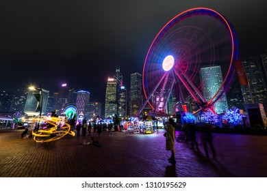Central, Hong Kong  - January 08, 2019 :  People ride ferris wheel in front of Hong Kong Business District at Night