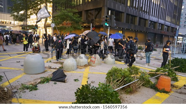 Central, Hong Kong - November 13, 2019: A road block made out of concrete planters and plants in the middle of an intersection downtown with protestors carrying umbrellas