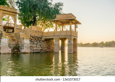 Central island park with sandstone buildings and trees growing at gadi sagar jaisalmer. The central island park is accessed through this gate and has multiple balconies to view the lake