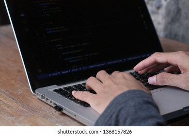""""""" Central java 13 April 2019 """" a male programmer is working on making an application on a laptop, a picture from above"""