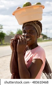 CENTRAL KALAHARI GAME RESERVE, BOTSWANA, DEC 28: Portrait of beautiful black African women walking with headscarf and fruits on her head, traditional village in the background. Botswana 2019