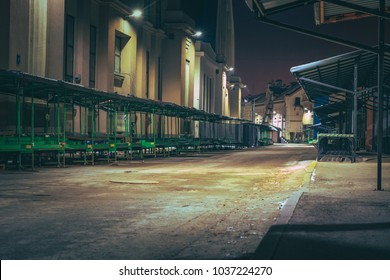 Central marketplace at night time. Isolated territory filled with trading stands and lighten by city lights. Spooky and abandoned atmosphere in urban market territory.