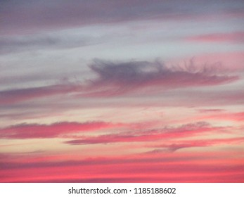 Central NJ/USA - August 2, 2018: The setting sun turns the sky a vibrant red and yellow color as clouds swirl overhead.