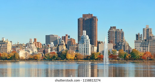 Central park Manhattan east side luxury building panorama over lake with fountain in Autumn in New York City.