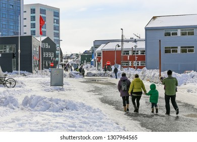 Central pedestrian street with modern building and walking people of Nuuk city, Greenland