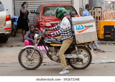CENTRAL REGION, GHANA - Jan 17, 2017: Unidentified Ghanaian man in helmet rides a motorcycle in local village. People of Ghana suffer  poverty due to the bad economy