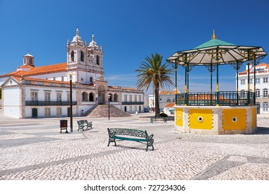 The central square of Nazare with pavilion and  Nossa Senhora da Nazare Church on the background. Portugal