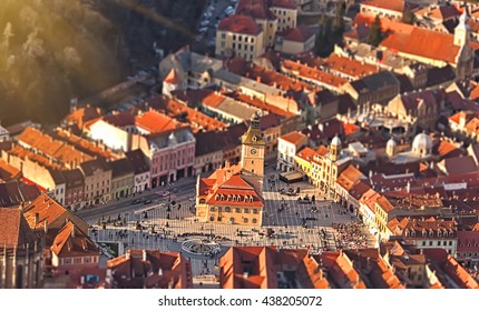 the central square of the old town. Brasov. Transylvania. View from above. The buildings, the people. An interesting effect. Evening sunlight. Old Square, people strolling on it, an old clock tower