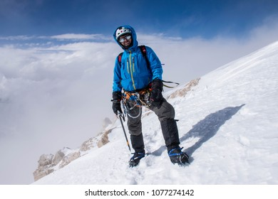 Central Tian Shan/Kazakhstan - Aug 2017: The russian climber Alex Volvach on the top of Khan-Tengry peak in Tian-Shan in the blue jacket and white helmet.
