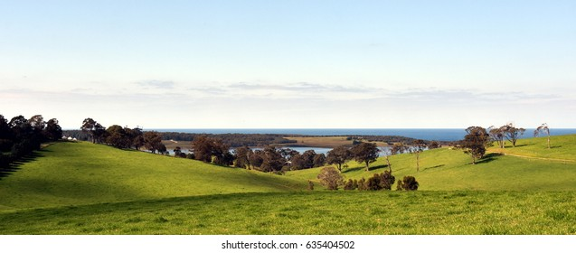 Central Tilba in its idyllic setting near Narooma. Autumn scene in rural New South Wales Australia. Farmland fields, trees, ponds and hills.