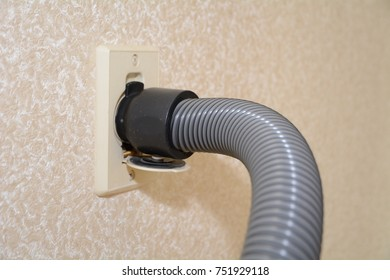 Central vacuum cleaner hose connected to the wall