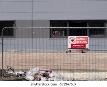 Central Way, Feltham, Middlesex, England - July 17, 2017: Danger no entry sign mounted on security fencing, new commercial warehouse and office development