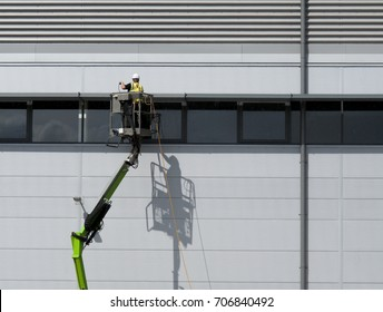 Central Way, Feltham, Middlesex, England - August 31, 2017: Construction worker on mobile boom lift cleaning external rainscreen cladding on new build office and warehouse development