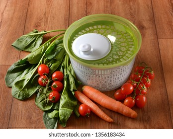 Centrifugal dryer for salad with vegetables around - closeup