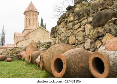 Centuries-old Kvevri, traditional Georgian clay winem aking pots, lined up along a stone wall outside a monastic school and monastery in the wine country of Telavi, Georgia.
