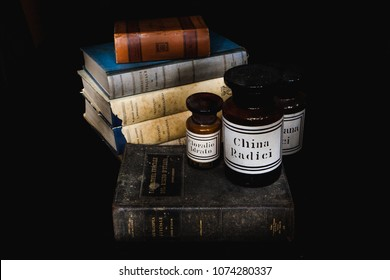 Century old books (Italian Pharmacopeia and Pharmacology books) and ancient glass pharmacy vases (Valerian, Chloral, Quinine). Light painting picture, black background.