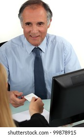 CEO handing business card to colleague