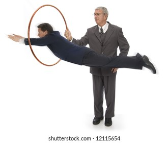 CEO holding up a hoop for his employee to jump through