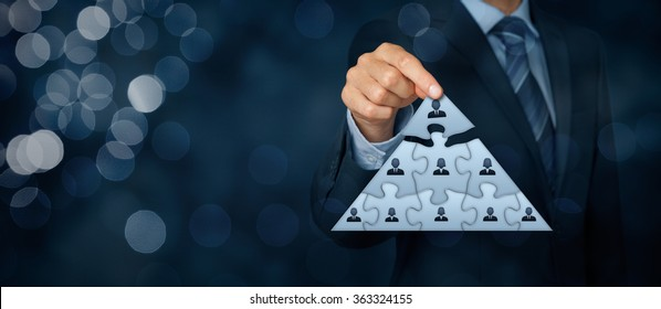 CEO, leadership and corporate hierarchy concept - recruiter complete team represented by puzzle in pyramid scheme by one leader person (CEO). Wide banner composition with bokeh in background.