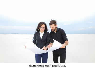 CEO male and CFO female holding whatman paper, colleagues discuss project of wind power plant in deserted place. Young woman and bearded guy standing among sands looking around. Concept of explor