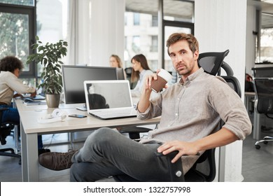 CEO with serious facial expression sitting in office and drinking coffee to go. In background employees working.