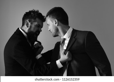CEOs fight for business on light grey background, facing each other. Conflict and business concept. Businessmen wear smart suits and ties. Men with beard and furious faces have quarrel.