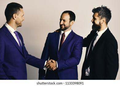 CEOs shake hands on light grey background. Business agreement and compromise concept. Businessmen wear smart suits and ties. Men with beard and smiling faces make successful deal.